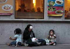 A homeless woman and her children sit outside a restaurant as she waits to receive a handout in Mexico City's historic Zocalo Square