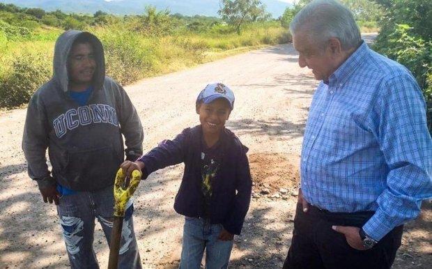El Presidente se detuvo a platicar con un hombre que pedía cooperación y tapaba un bache junto a su hijo en Axochiapan.