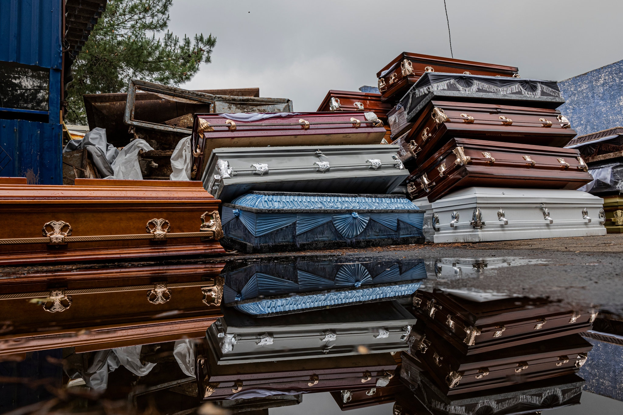 Féretros de víctimas recientes de COVID-19 apilados en la parte trasera de un crematorio en el panteón de Xilotepec en XochimilcoCredit...Daniel Berehulak para The New York Times